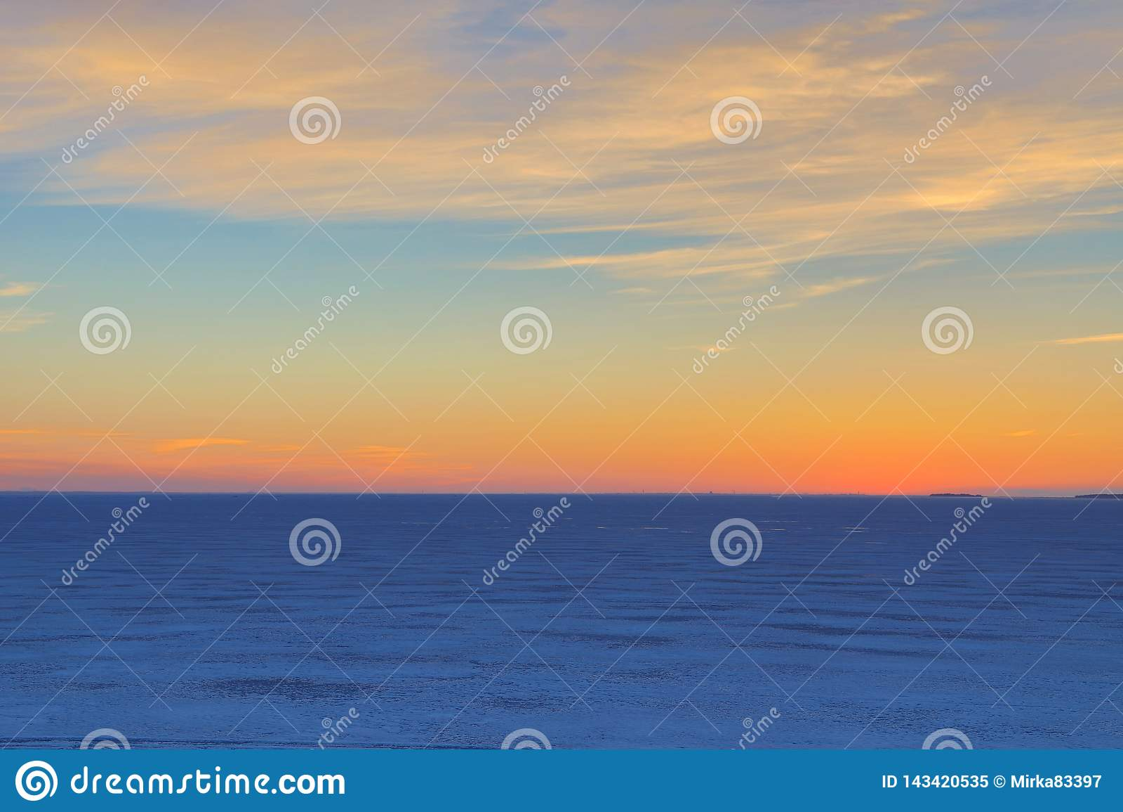El cielo nublado cloured en coloures brillantes y vivos rojos, anaranjados, carmesís, púrpuras, violetas y azules con el ajuste o