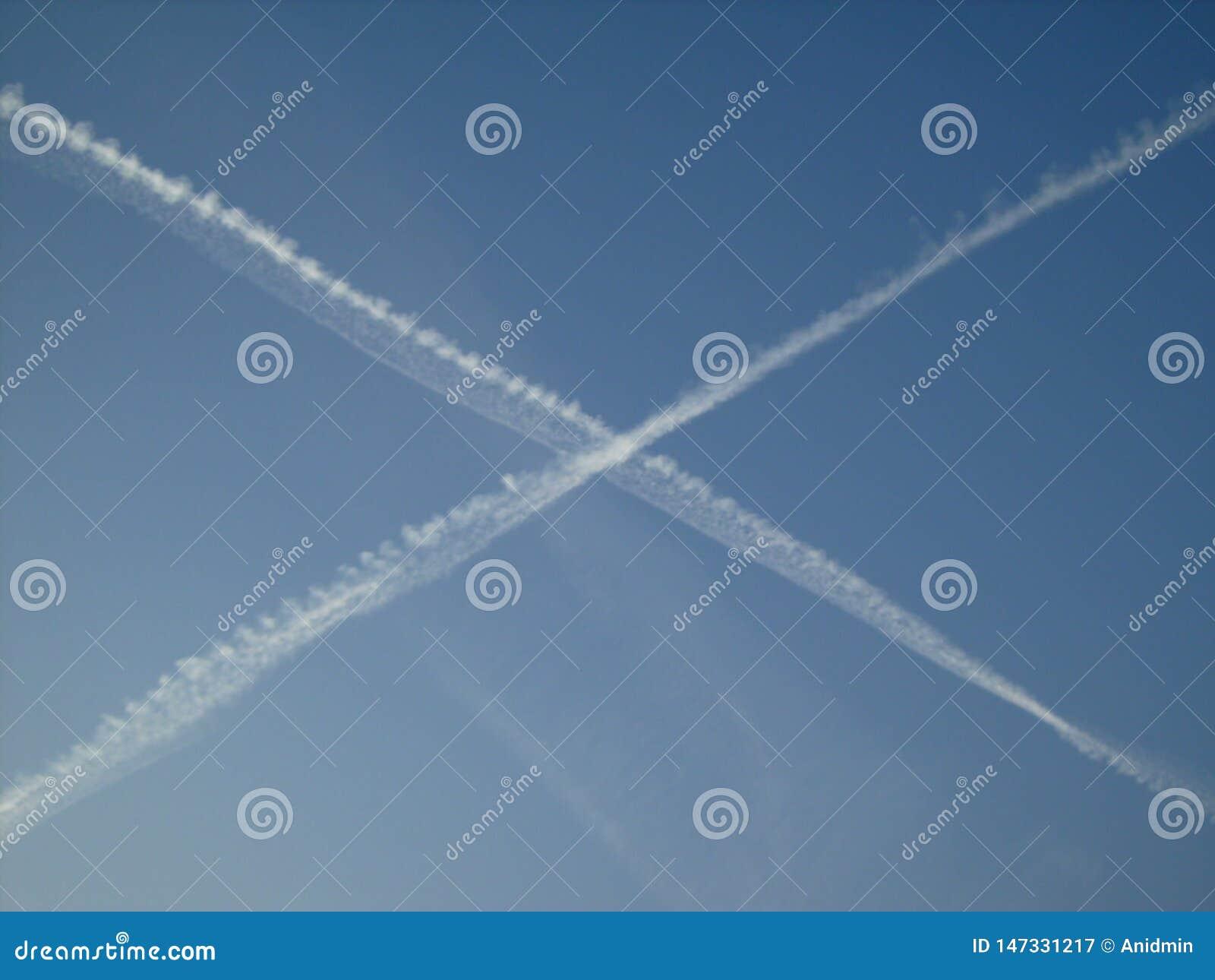 El cielo soleado azul cruzó con las pistas blancas del aeroplano