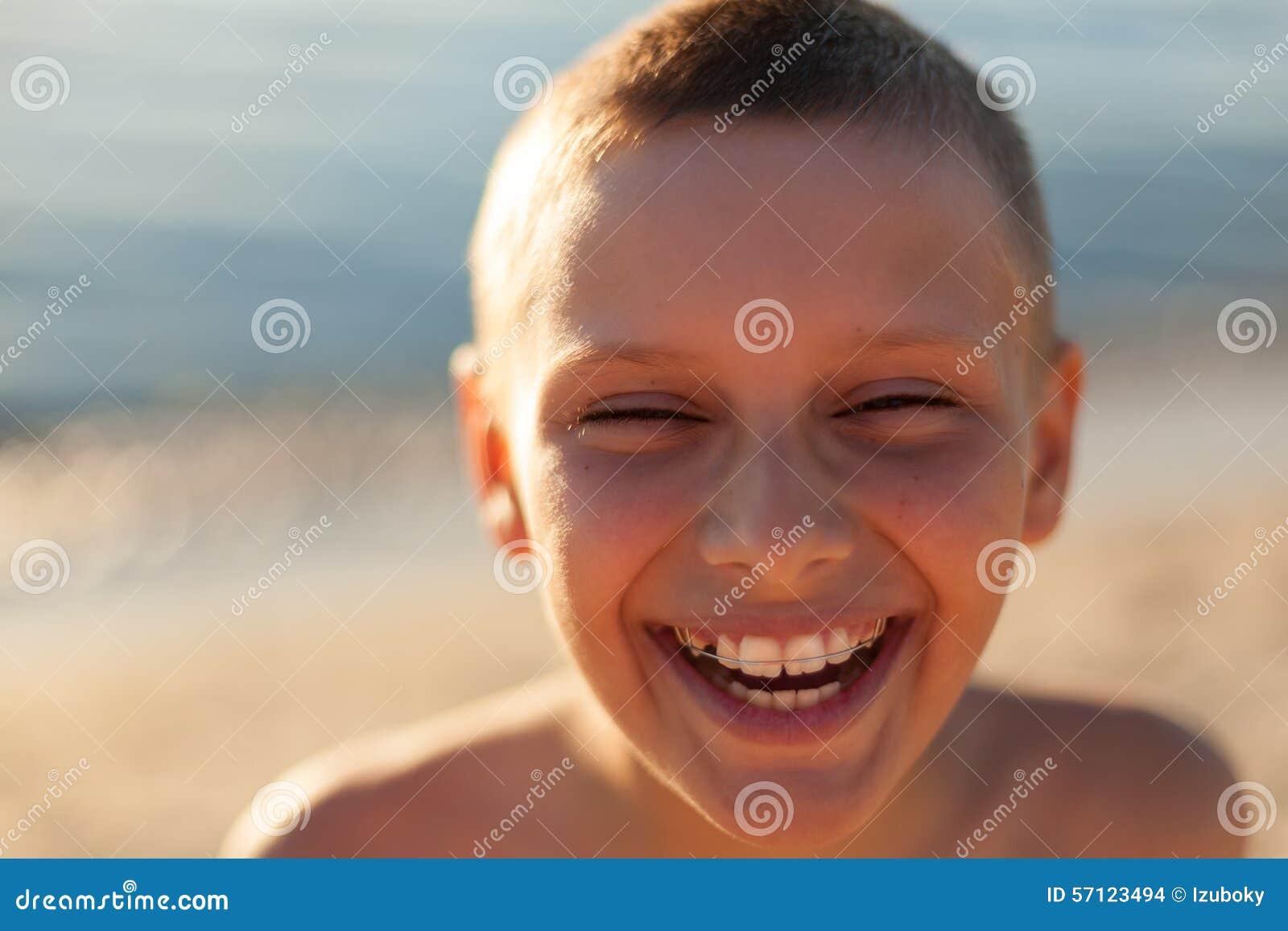 El cierre del retrato del muchacho del niño encima de la risa feliz del contraluz de la puesta del sol apoya los dientes