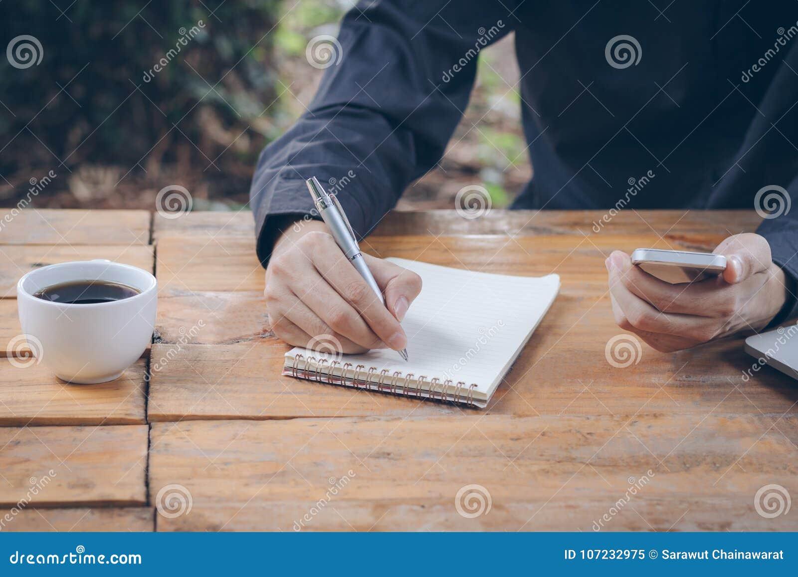 El cierre encima del hombre de negocios escribe el cuaderno y teléfono móvil con