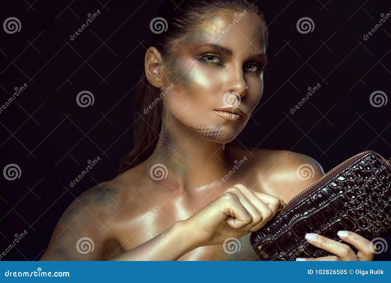 El cierre encima del retrato de la mujer magnífica con amarillo observa y el snakeskin artístico compone sostener el monedero del