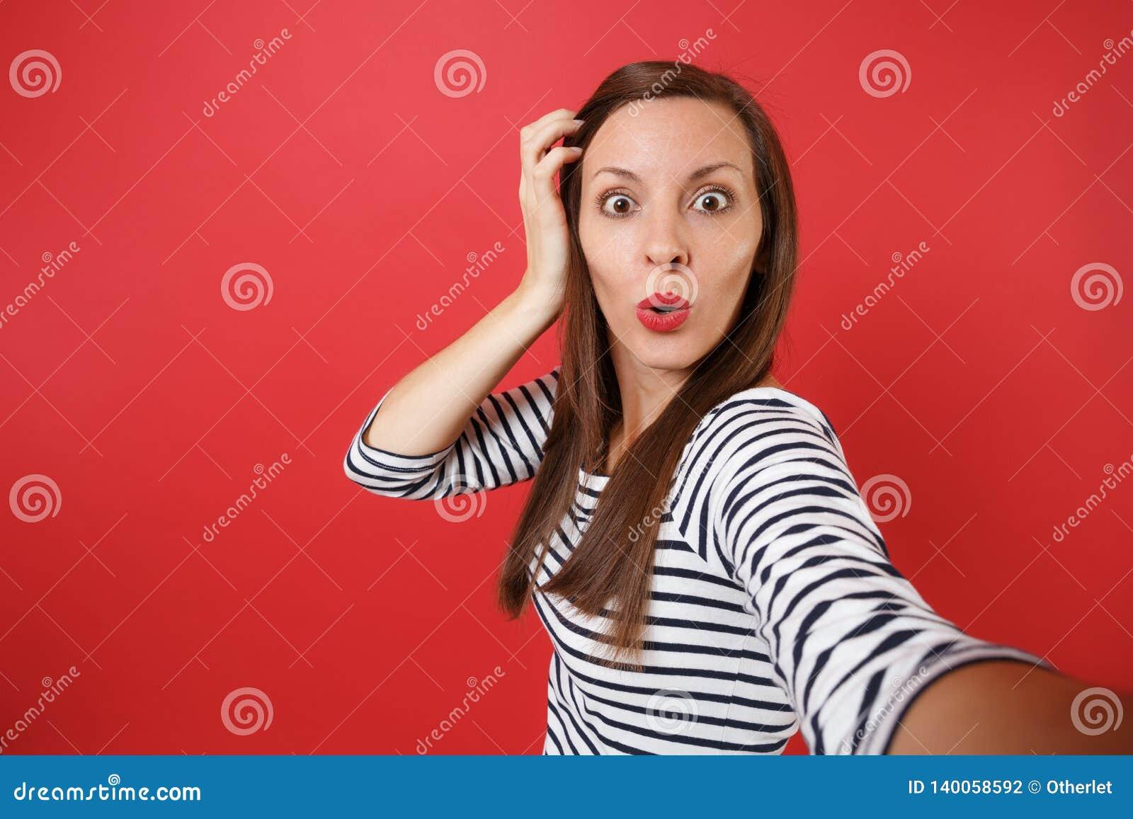El cierre encima del selfie tirado de mujer joven chocada en la ropa rayada que guardaba la mano cerca de la cabeza, mirando sorp