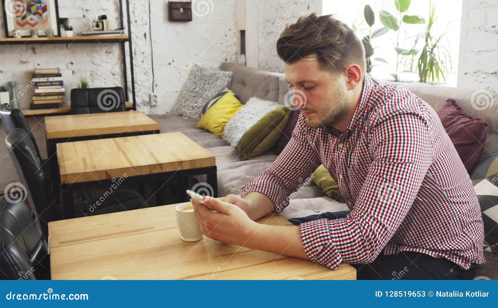 El cliente está utilizando su teléfono mientras que bebe el café