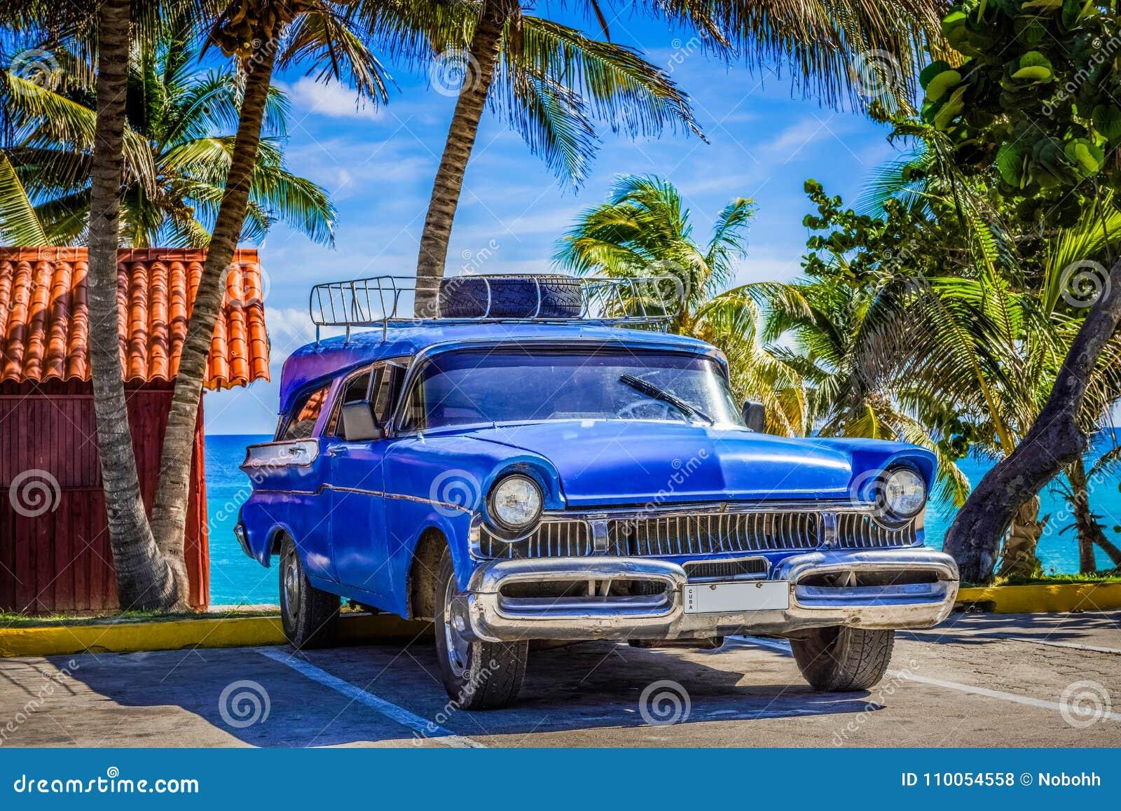 El coche clásico azul americano parqueó en la playa en Varadero Cuba - el reportaje de Serie Cuba