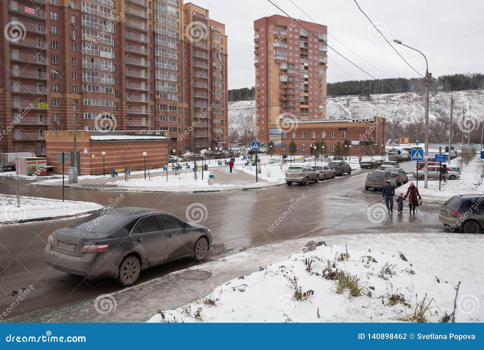 El coche condujo para arriba a la intersección con un paso de peatones en el microdistrict con las construcciones de viviendas de