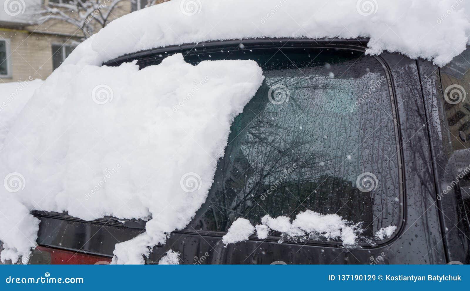 El coche, cubierto con la capa gruesa de nieve Consecuencia negativa de nevadas pesadas coches parqueados cubiertos con nieve dur