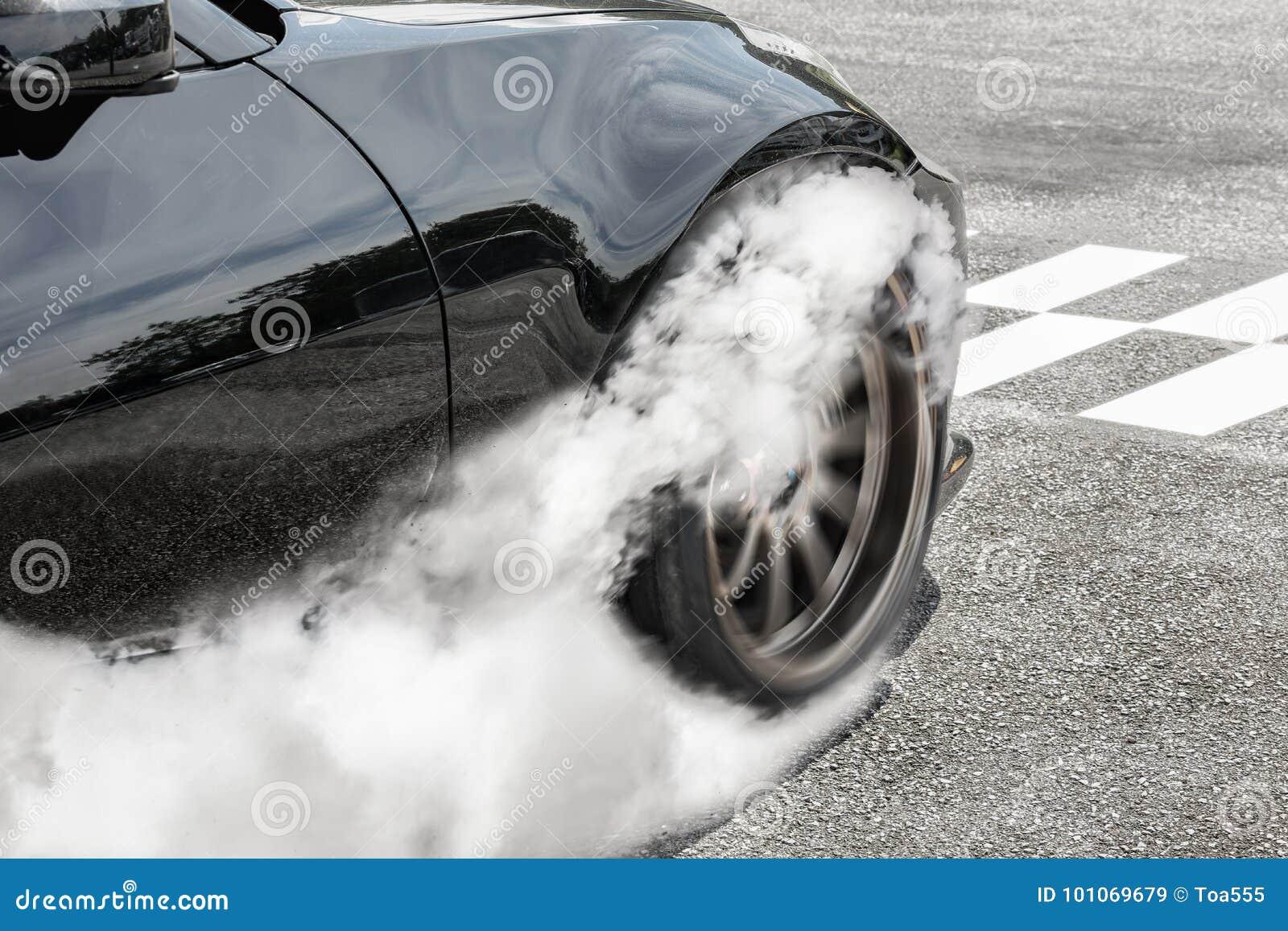 El coche de competición de la fricción quema los neumáticos en la línea del comienzo