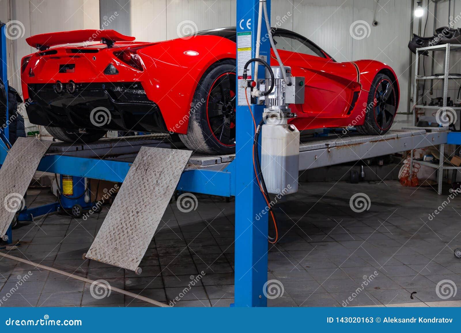 El coche de deportes rojo aumentó en una elevación en un taller de reparaciones, un parachoques trasero y un alerón del coche