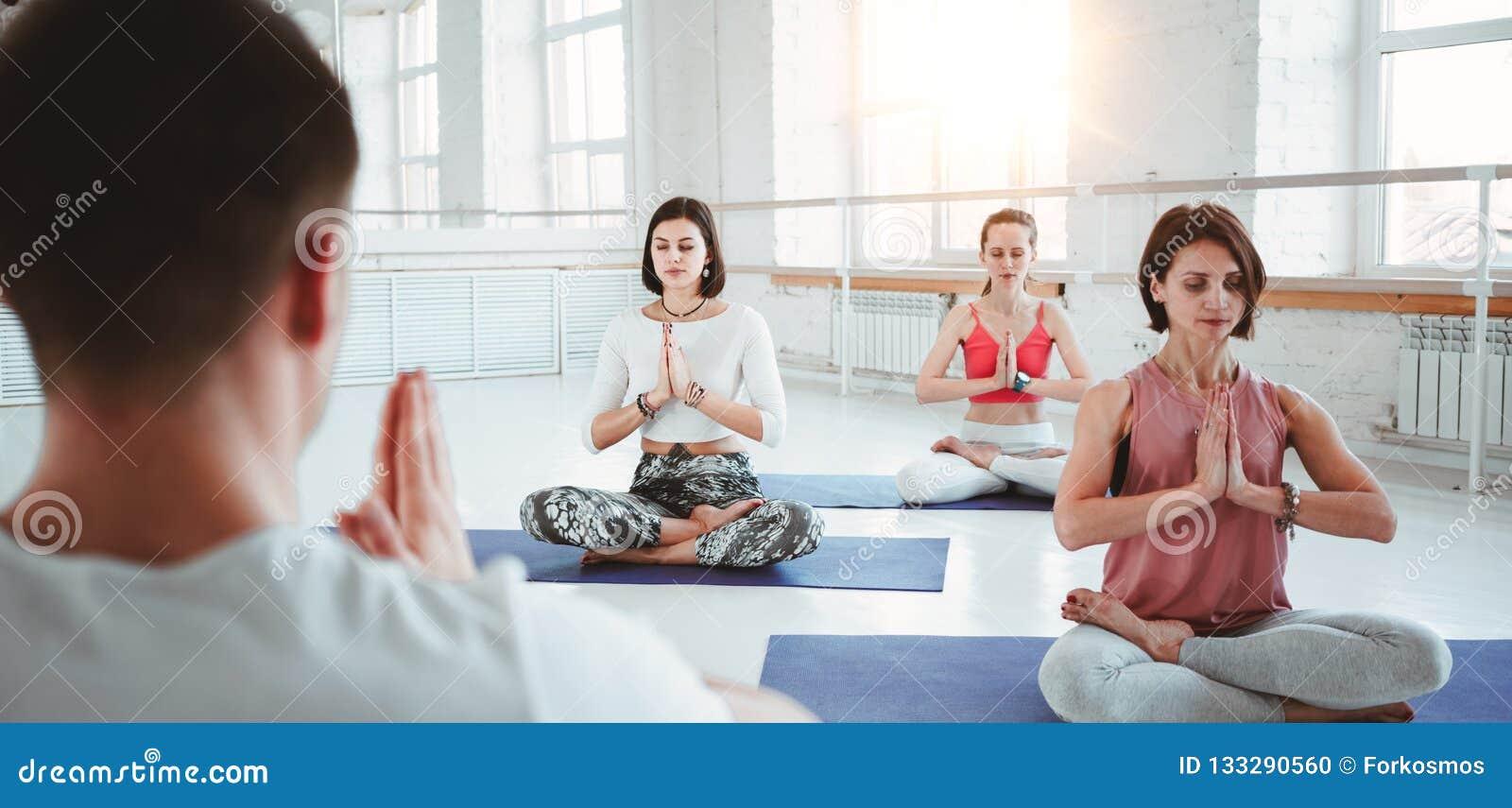 El coche del hombre entrena al grupo de ejercicios de la yoga de las mujeres para la atención sanitaria que mantiene en la clase