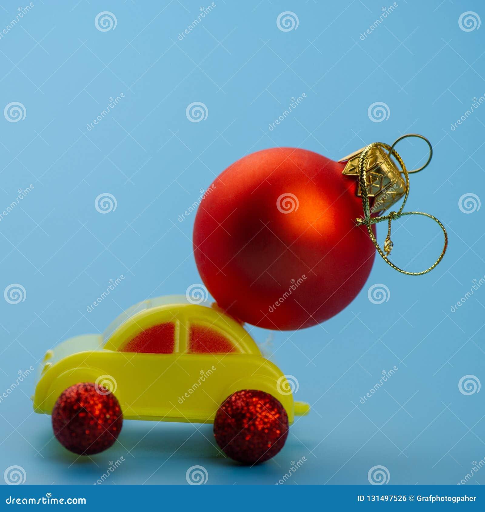 El coche del juguete lleva una bola roja del árbol de navidad