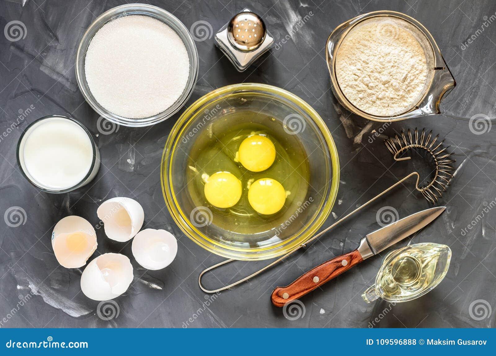 El cocinar del ruso sirve las crepes: huevos, leche, harina, mantequilla, sal