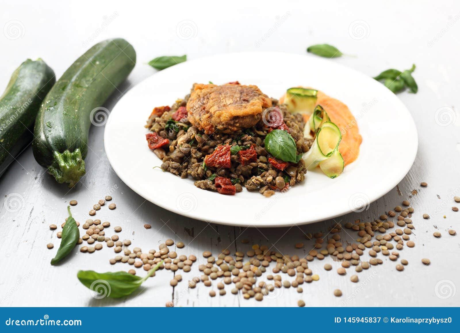 El cocinar vegetariano Plato meatless vegetal colorido Lentejas hervidas con pur? de la zanahoria y el calabac?n asado a la parri