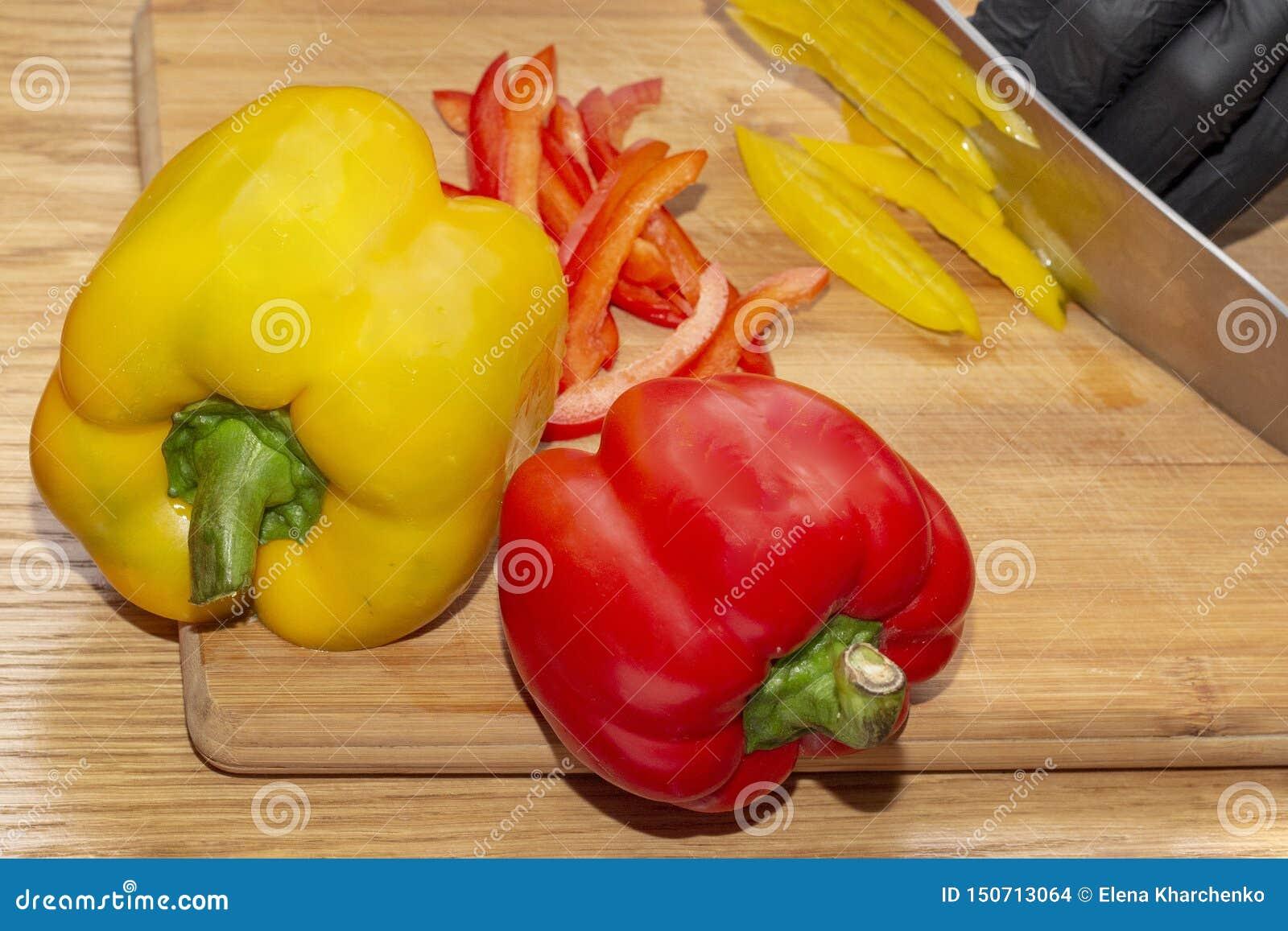 El cocinero corta las pimientas de la paprika en plato dietético vegetariano en guantes en una tabla de cortar de madera