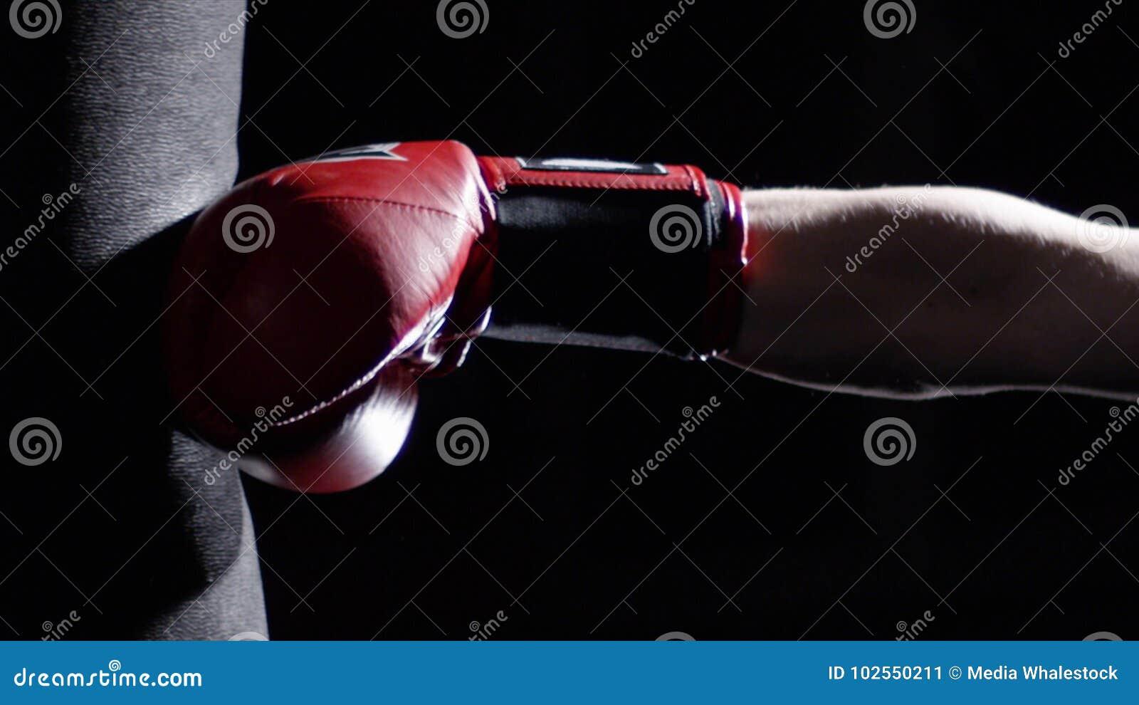 El combatiente que practica alguno golpea con el pie con el saco de arena - hombre con un boxeo del tatuaje en fondo oscuro Retro