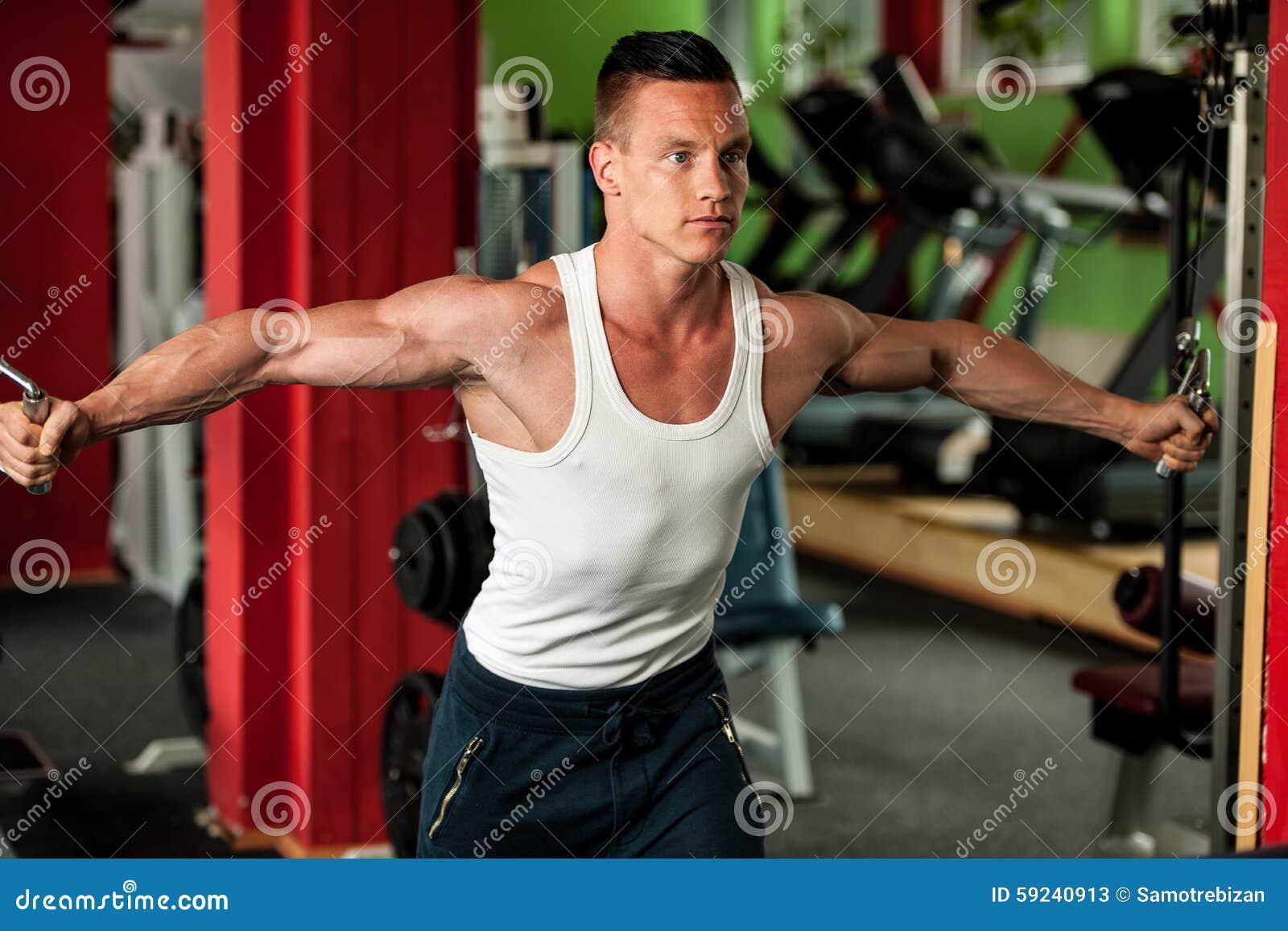 El competidor de la aptitud de Phisique se resuelve en pesas de gimnasia de elevación del gimnasio