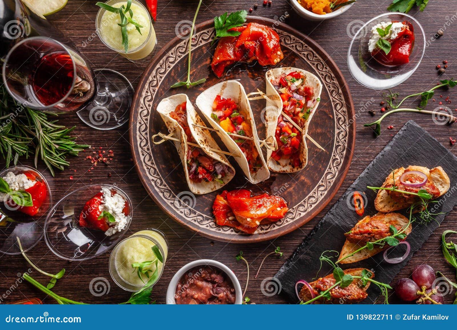 El concepto de cocina mexicana Comida y bocados mexicanos en una tabla de madera Taco, sorbete, tártaro, vidrio y botella de vino