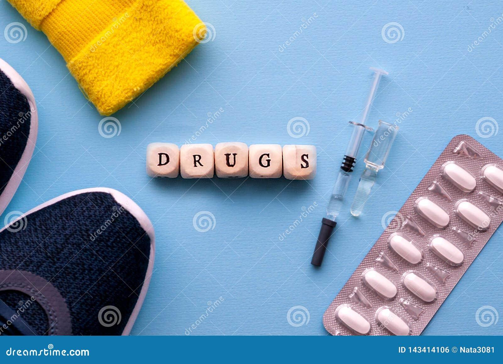 El concepto de doping en deporte La inscripción arrastra en un fondo azul Zapatos de los deportes, píldoras, jeringuilla con la m