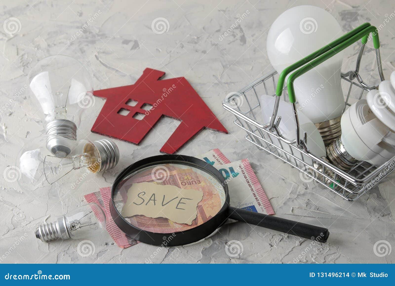 El concepto de electricidad del ahorro dinero, casa decorativa y diversas bombillas en una cesta en un fondo ligero
