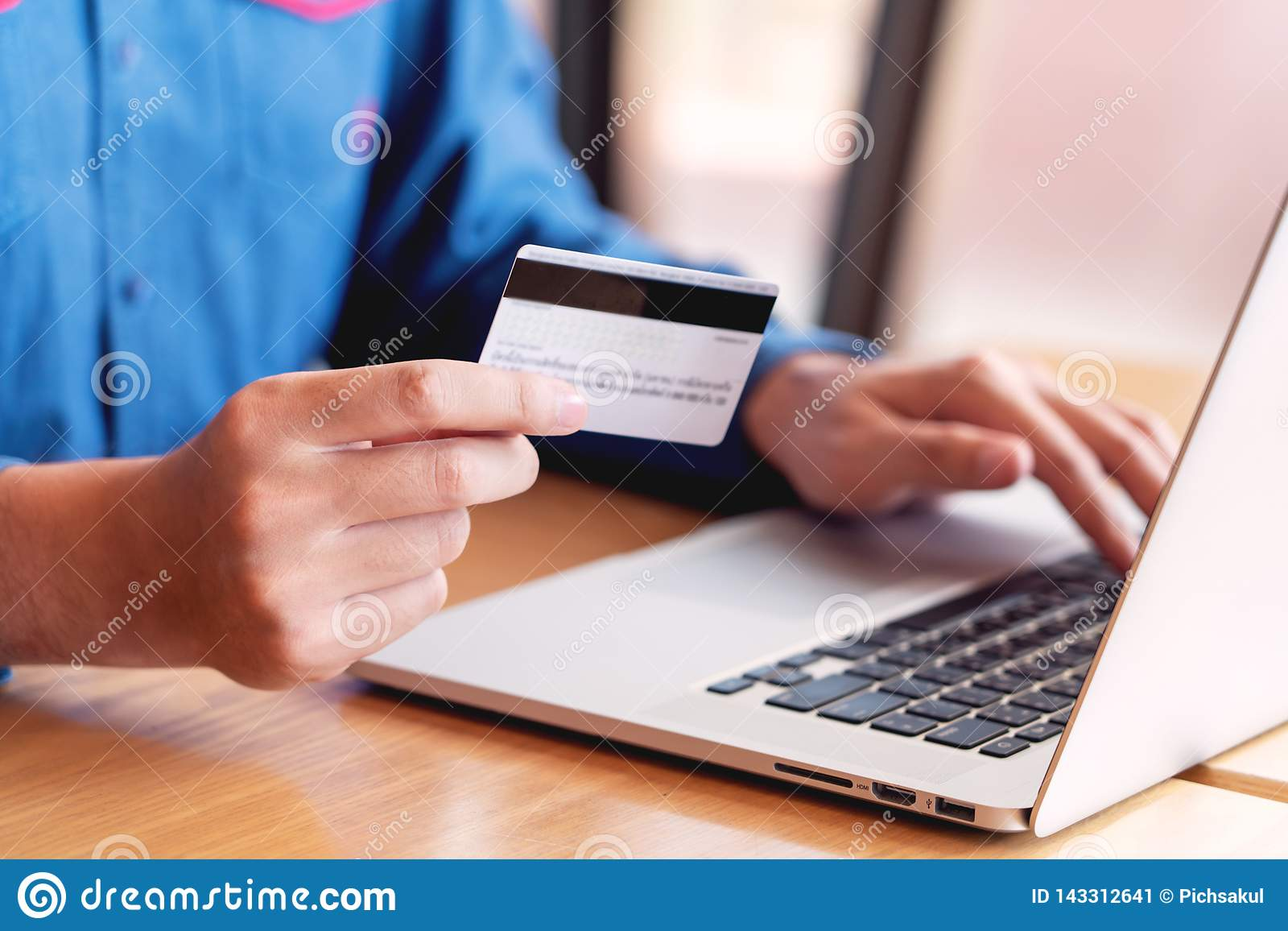 El concepto en línea de la seguridad de datos de la tarjeta de crédito que hace compras, da sostener la tarjeta de crédito y usar