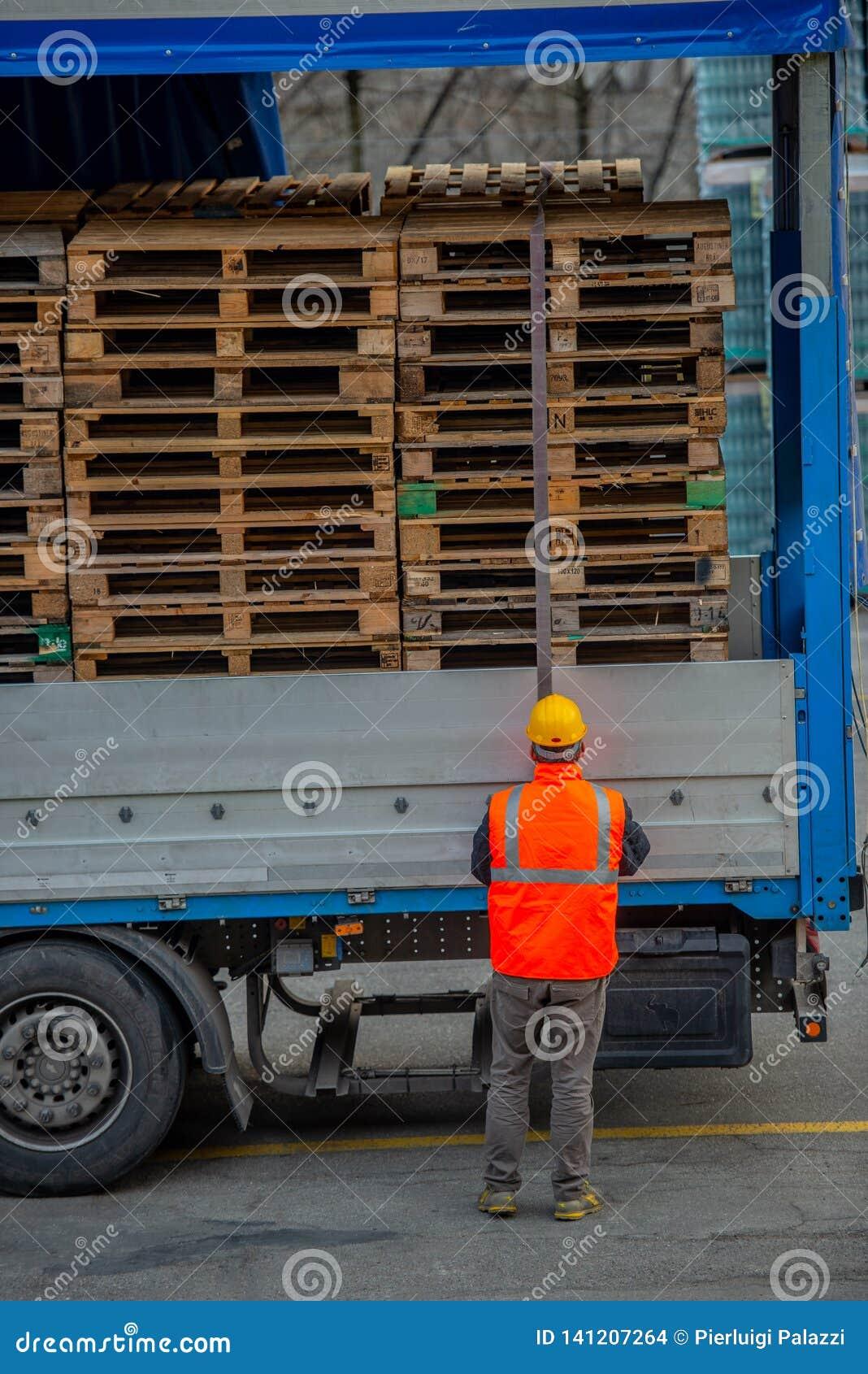 El conductor de camión asegura el cargamento de botellas de agua mineral atándolo con las cuerdas antes de comenzar el transporte