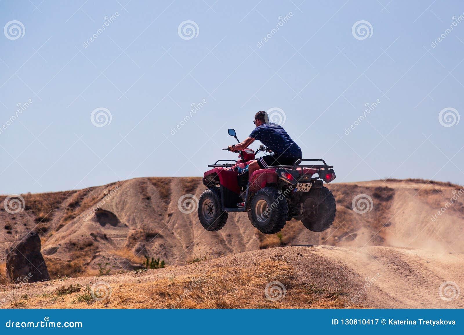 El conductor de las bicis del patio está saltando a través de la colina