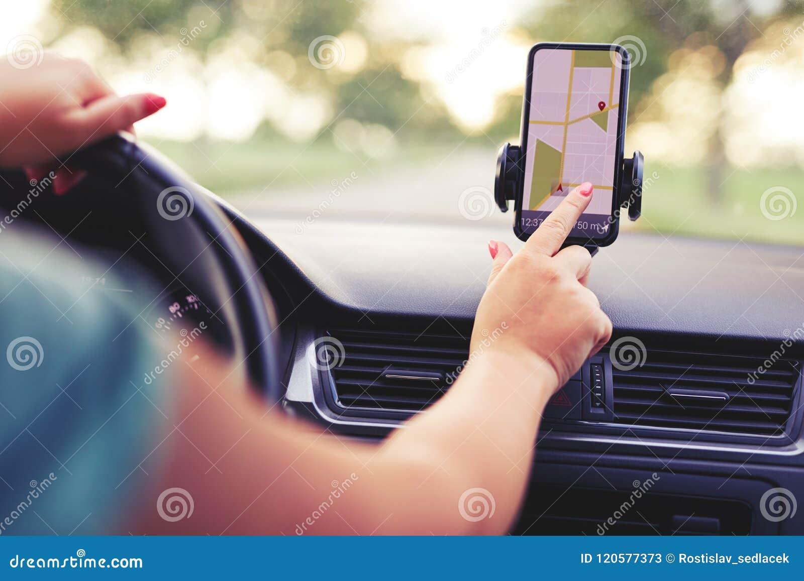 El conductor femenino utiliza la navegación en su teléfono móvil