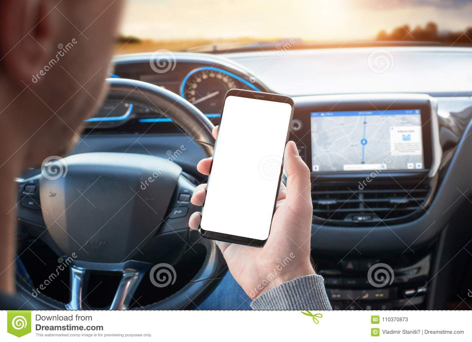 El conductor utiliza el teléfono mientras que conduce Teléfono elegante moderno con los bordes redondos