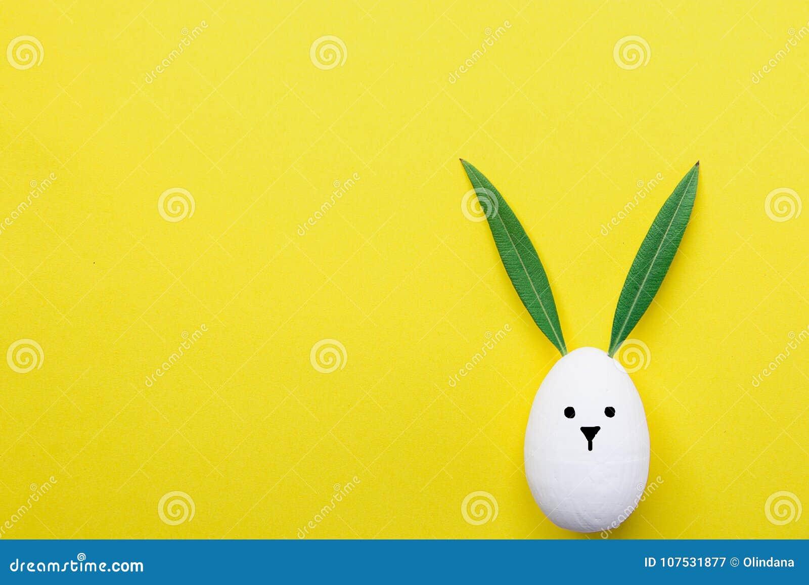 El conejito pintado blanco decorativo del huevo de Pascua con Kawaii lindo exhausto hace frente Hojas del verde como oídos Fondo