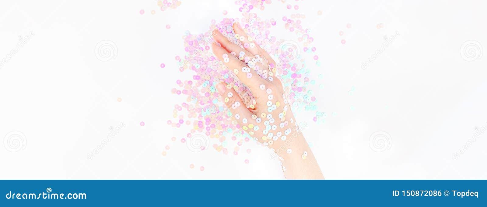 El confeti en colores pastel de la perla chispea con la mano de la mujer