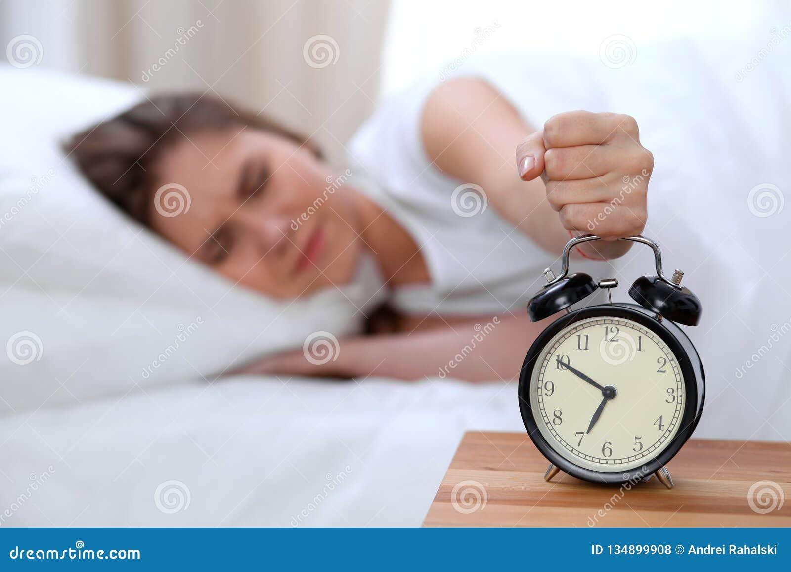 El contrario del despertador de la mujer joven soñolienta que estira la mano a querer de sonido de la alarma lo apaga Despierte t