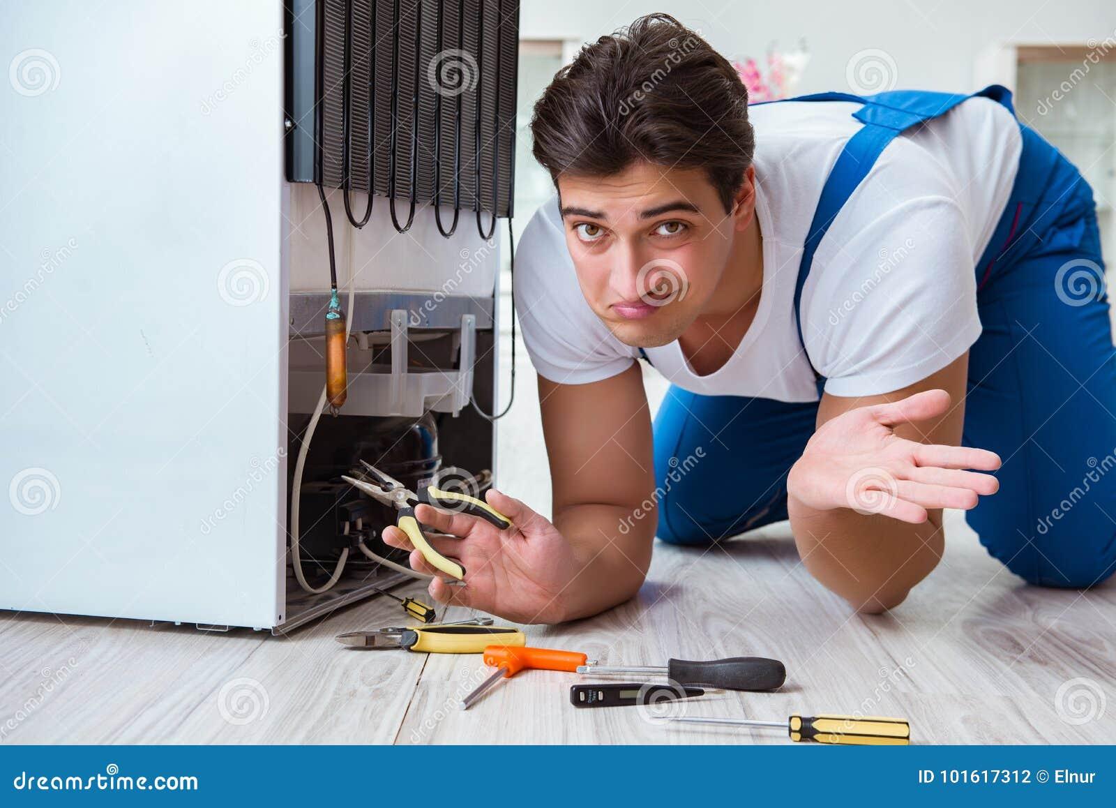 El contratista del reparador que repara el refrigerador en concepto diy