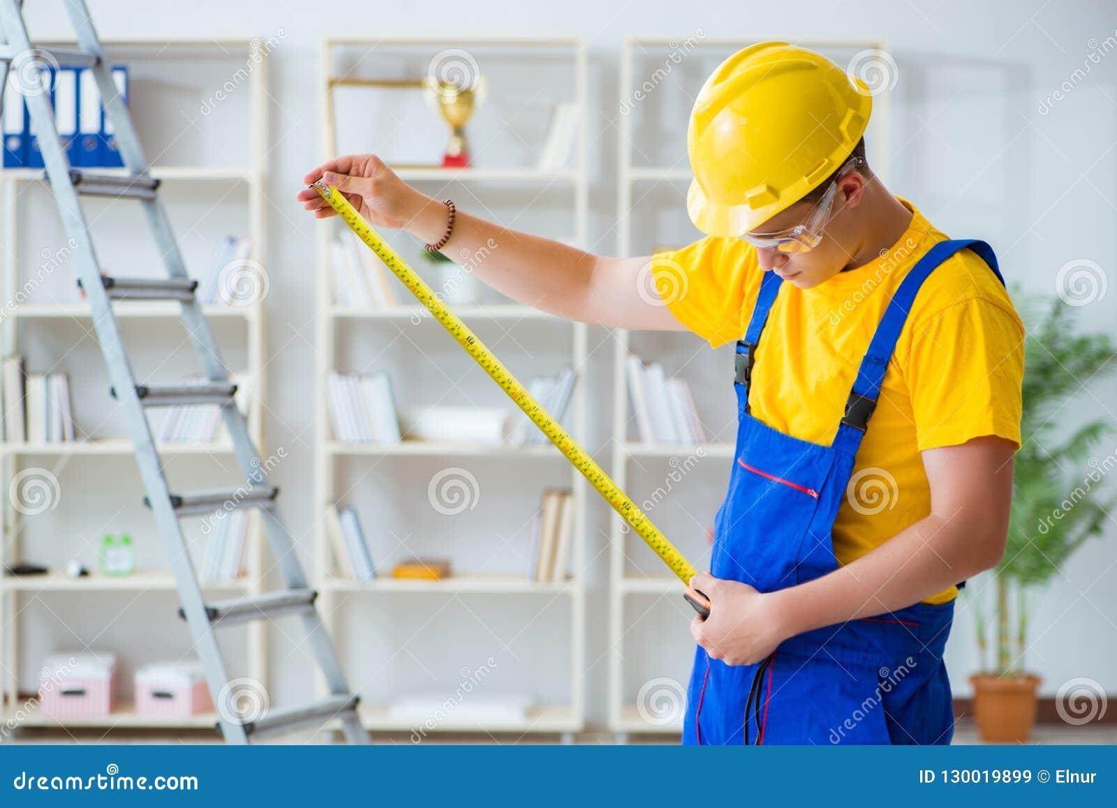 El contratista joven que hace la reparación trabaja en la oficina