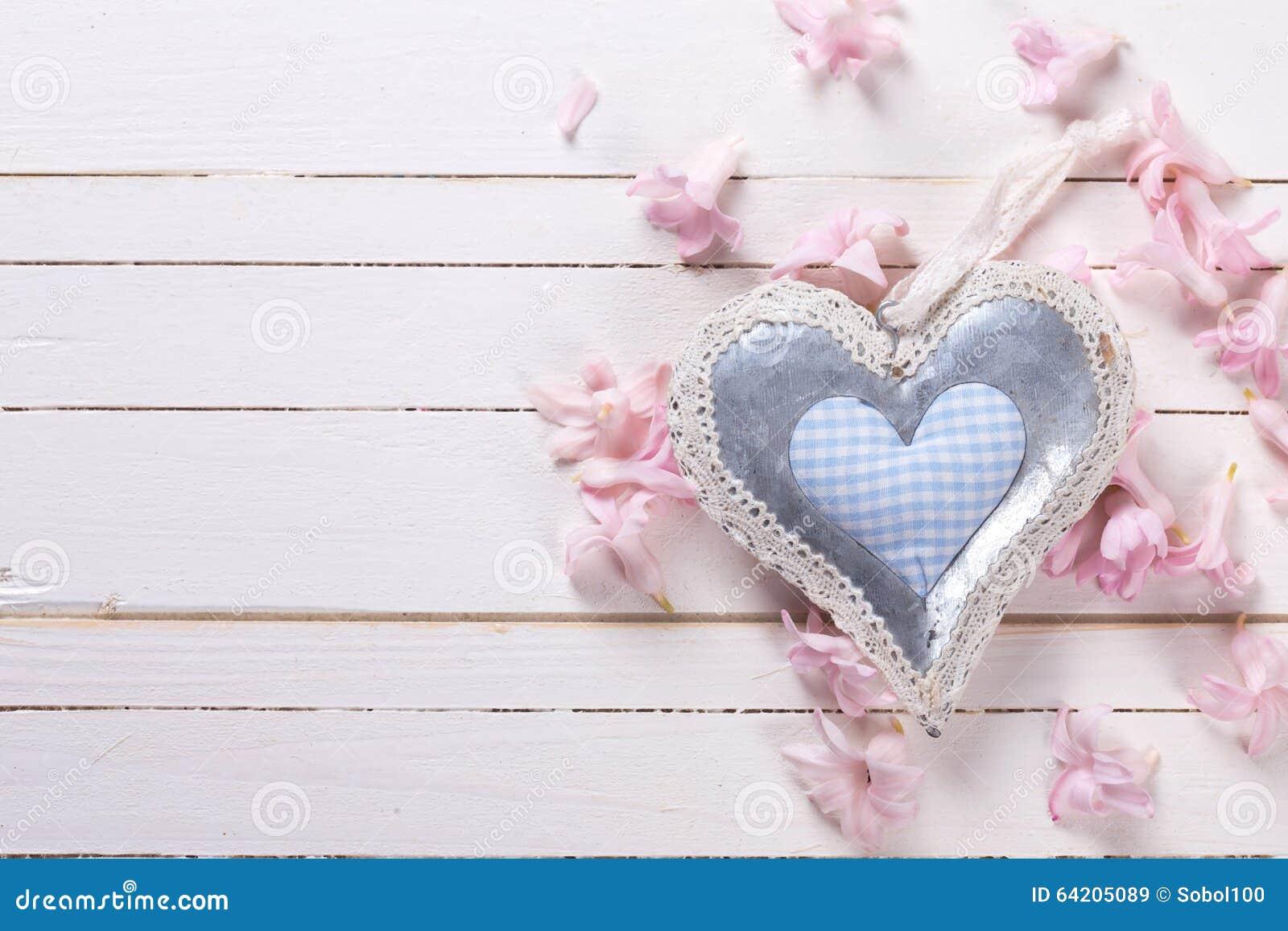 El corazón decorativo y las pequeñas flores rosadas en el blanco pintado cortejan