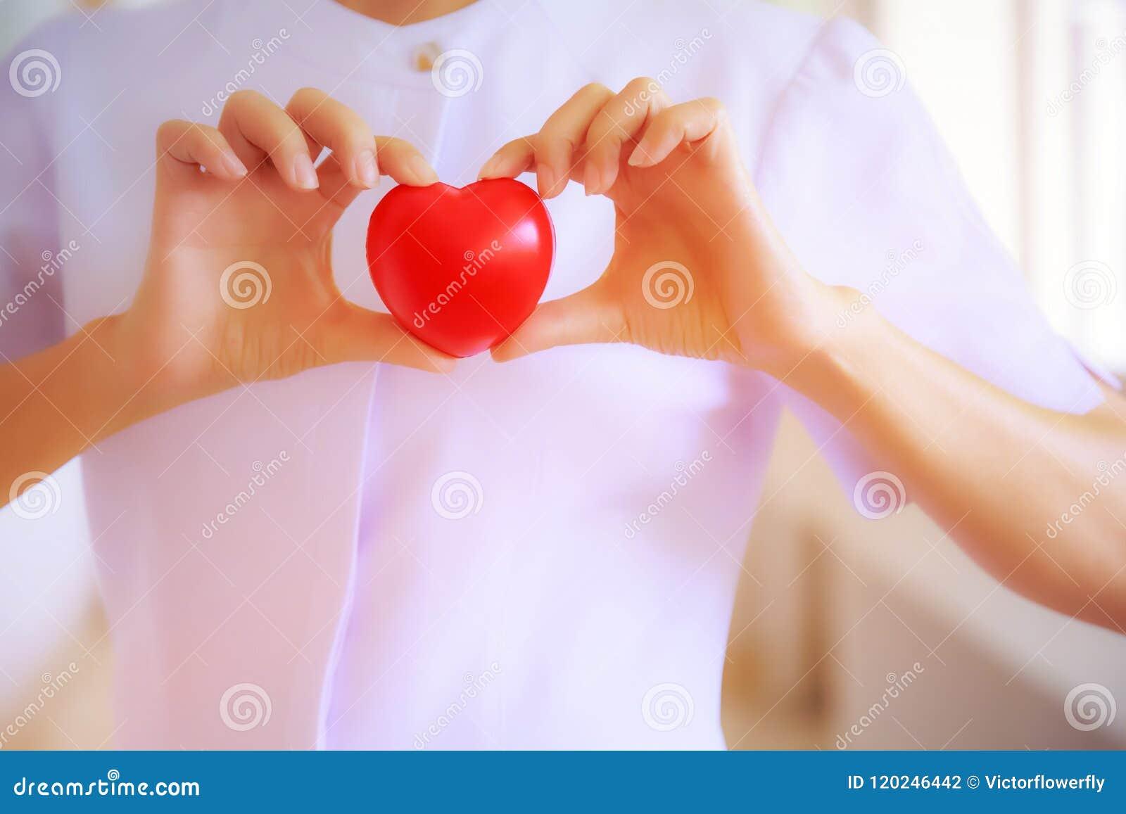 El corazón rojo se sostuvo por la mano femenina sonriente del ` s de la enfermera, representando dando a esfuerzo la mente de alt
