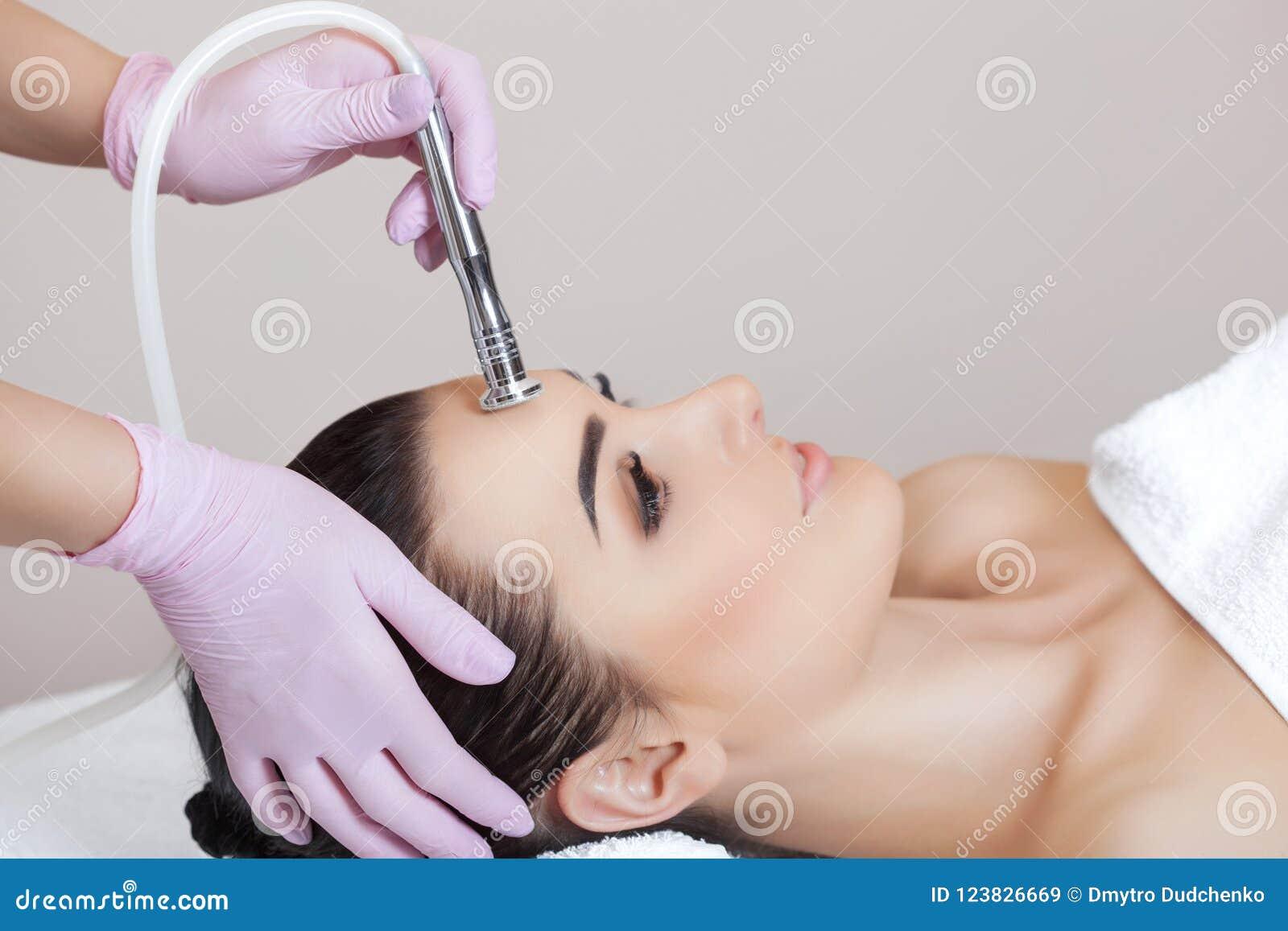 El cosmetologist hace el procedimiento Microdermabrasion de la piel facial de una mujer hermosa, joven en un salón de belleza