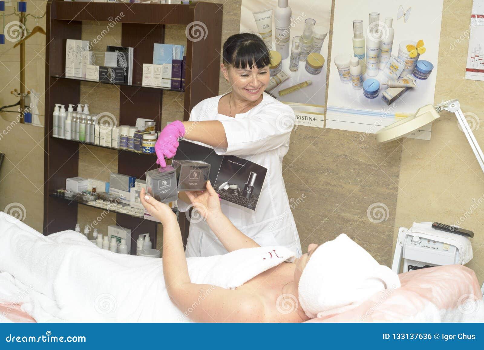 El cosmetologist ofrece los cosméticos del cliente, Ucrania, pueblo de Polyana, diciembre de 2018