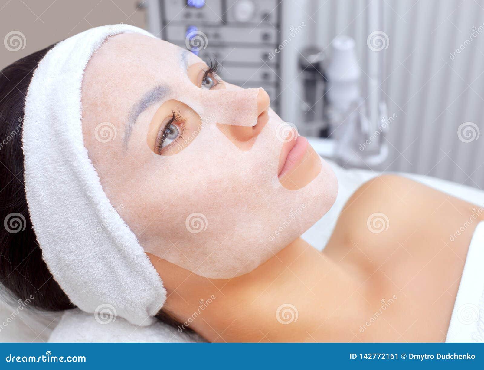 El cosmetologist para el procedimiento de limpiar y de hidratar la piel, aplicando una máscara de la hoja a la cara