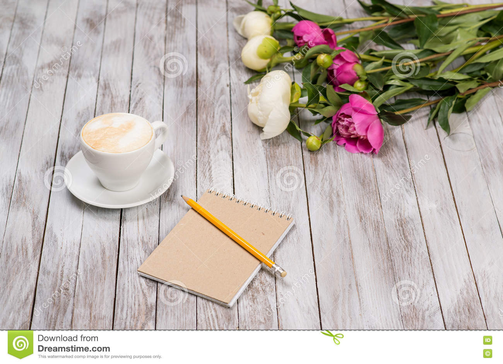El cuaderno con un lápiz al lado del café y de las peonías florece en fondo de madera