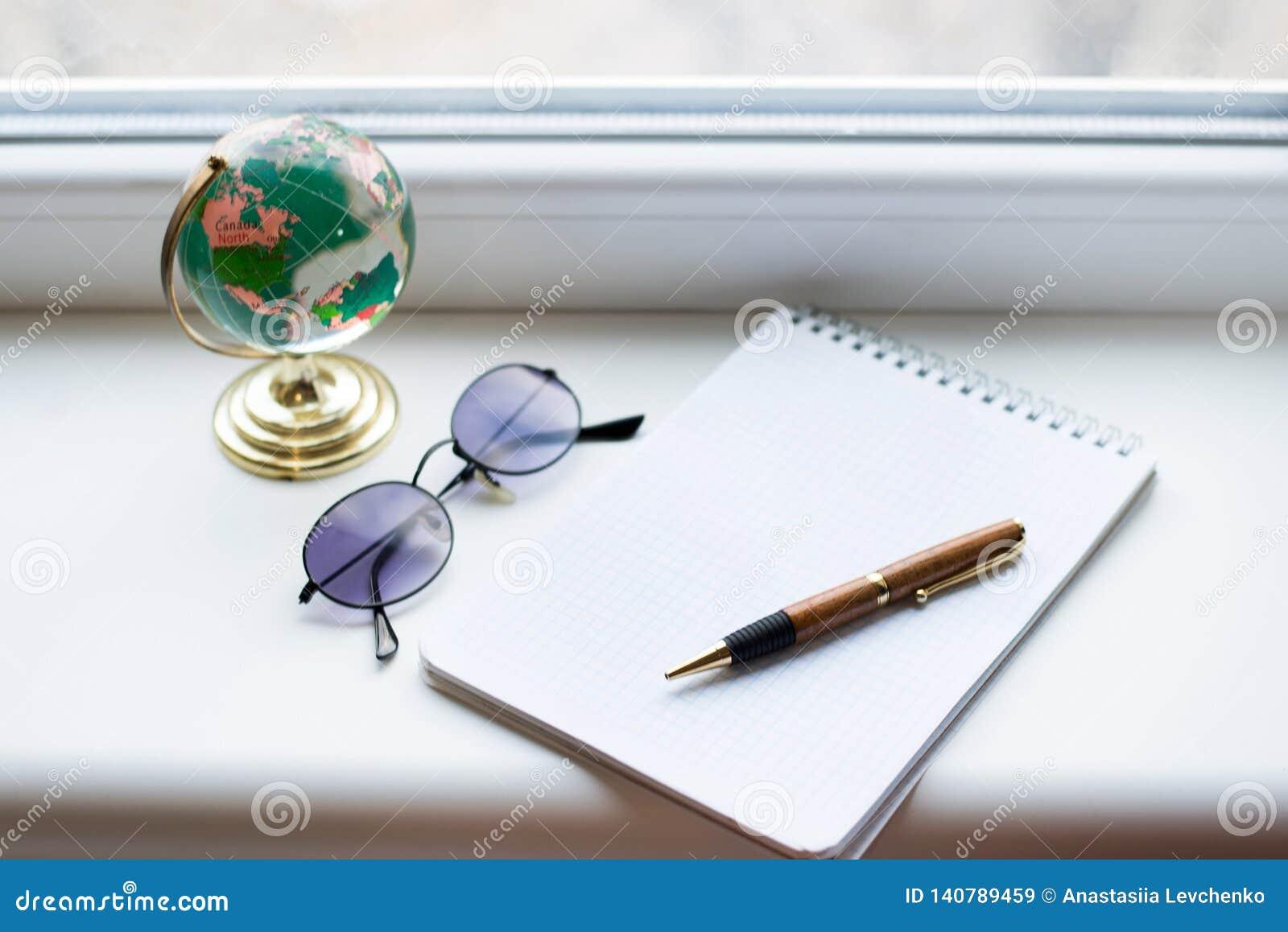 El cuaderno se abrió en el escritorio blanco con la pluma, el globo y los vidrios negros Visión desde arriba