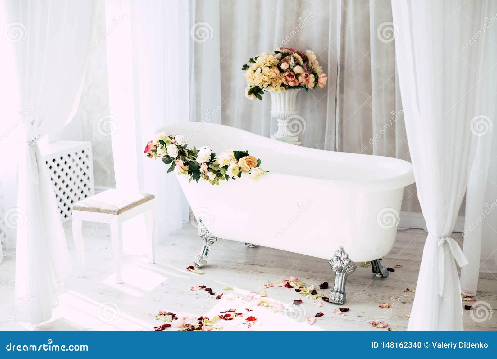 El cuarto de ba?o est? en un cuarto ligero adornado con las flores y los p?talos de rosas