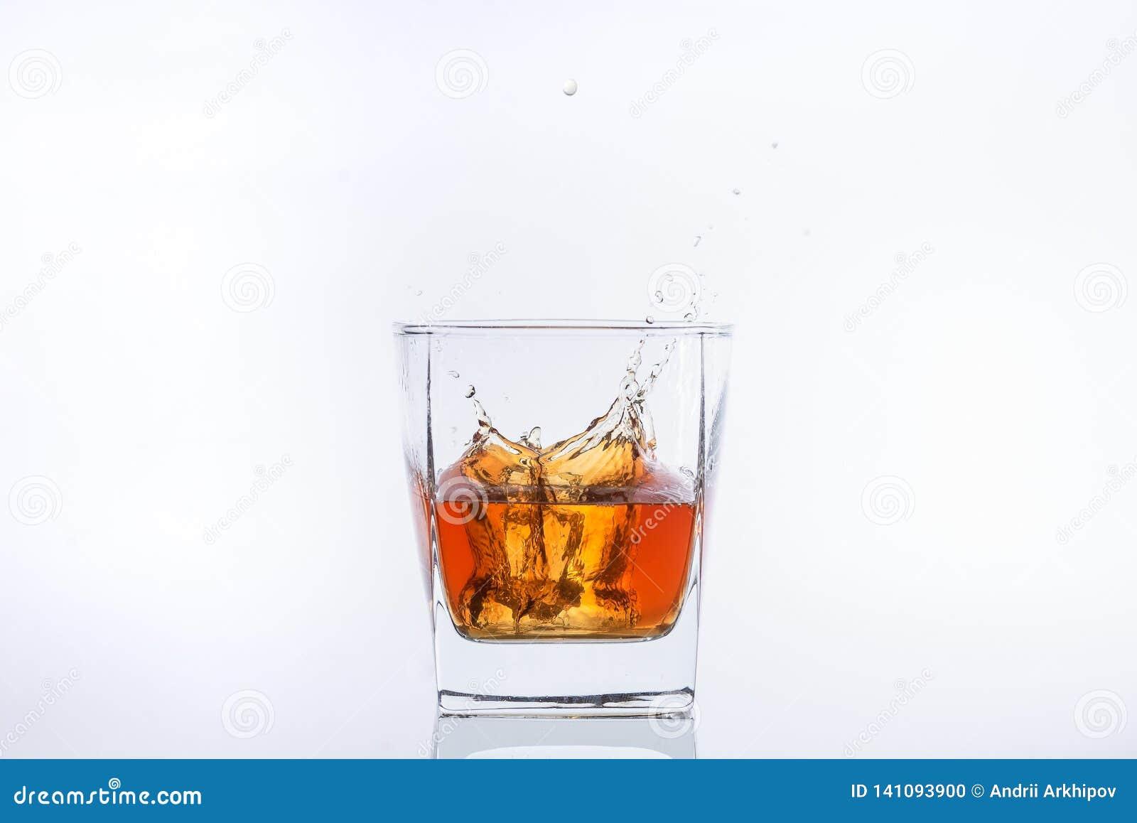 El cubo de hielo cae con salpica en un vidrio con alcohol
