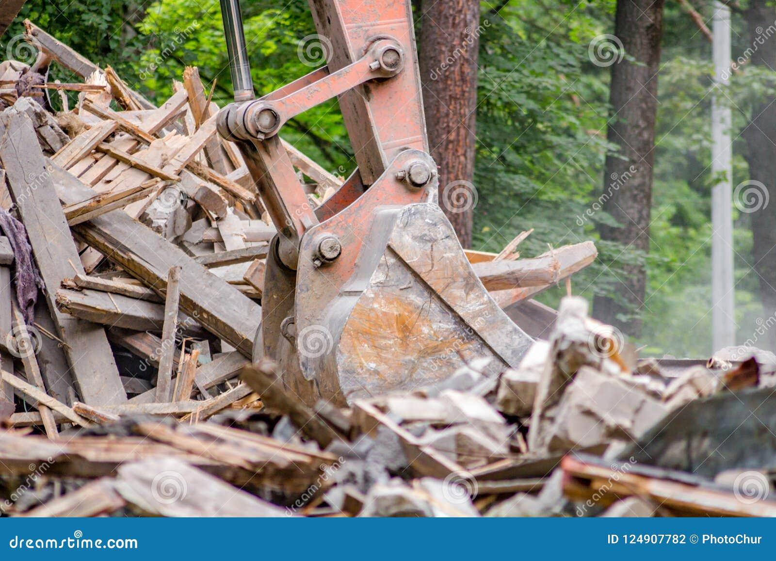 El cubo del excavador carga la ruina de construcción después de la demolición del edificio viejo