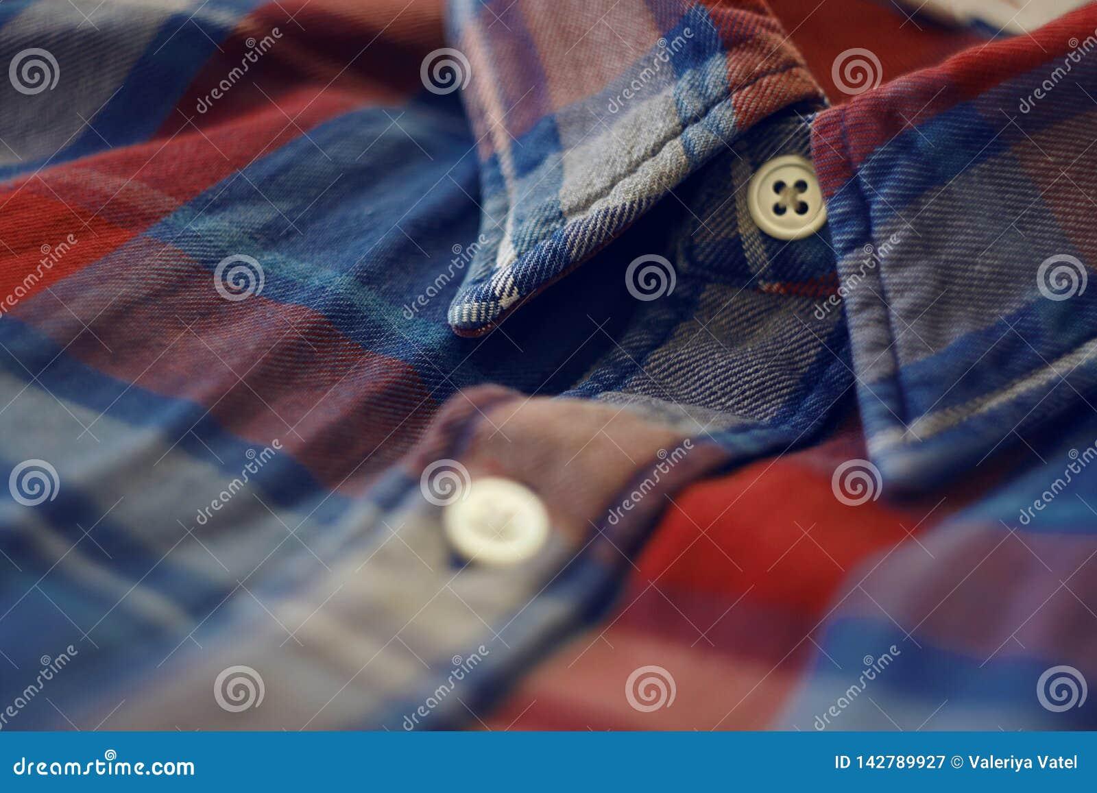 El cuello de la camisa a cuadros roja y azul, abotonado