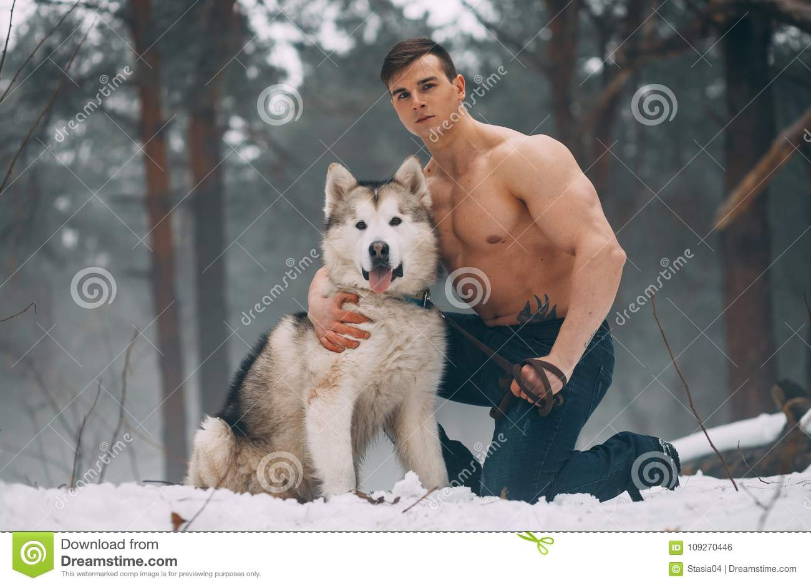 El culturista joven con el torso desnudo abraza el Malamute del perro en el paseo en bosque del invierno