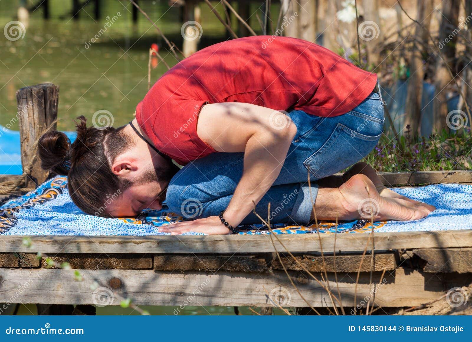 El día de verano de la yoga de la práctica del hombre joven del niño del lago presenta para la relajación