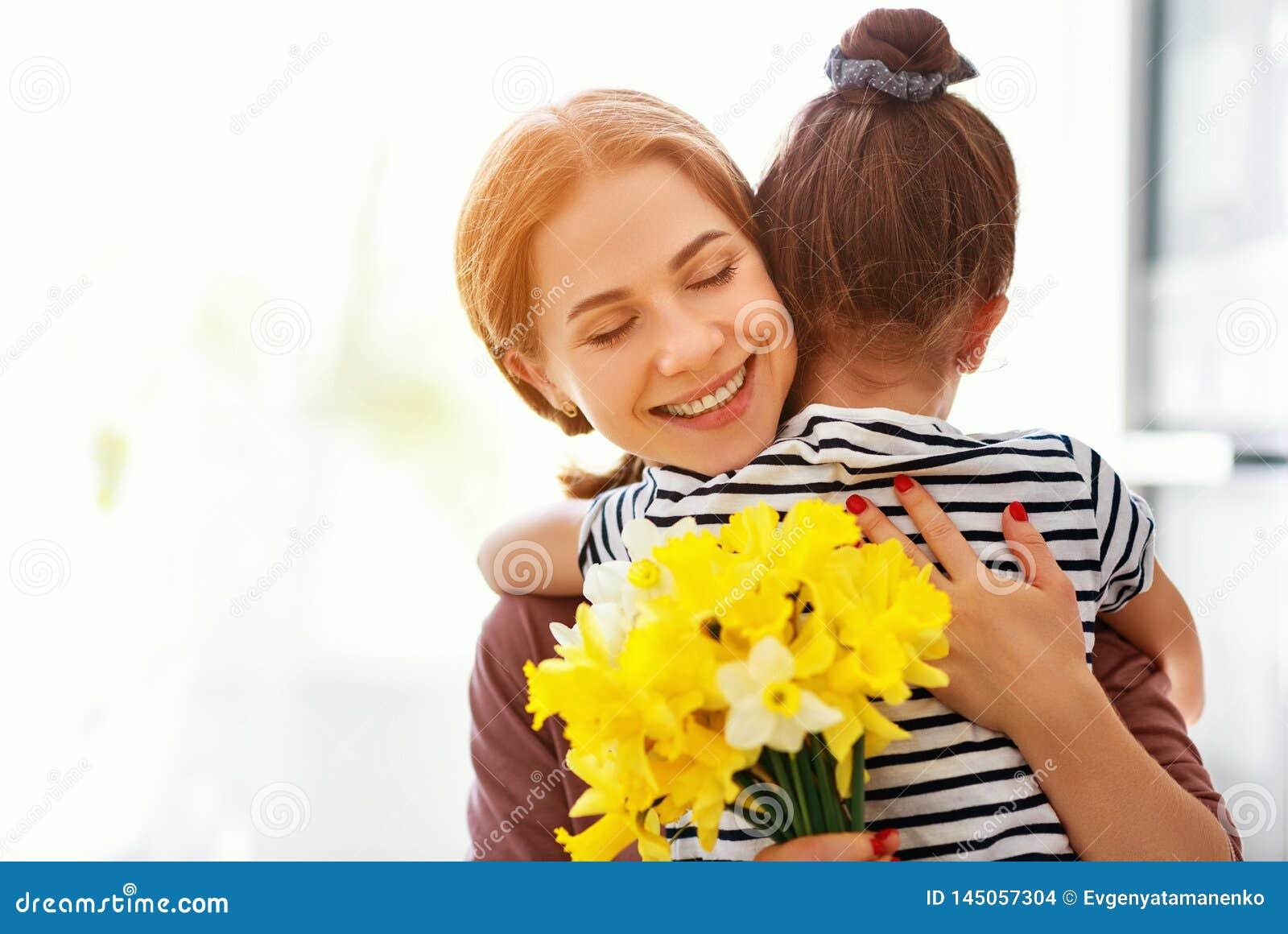 ?El d?a de madre feliz! la hija del ni?o da a madre un ramo de flores a los narcisos y al regalo