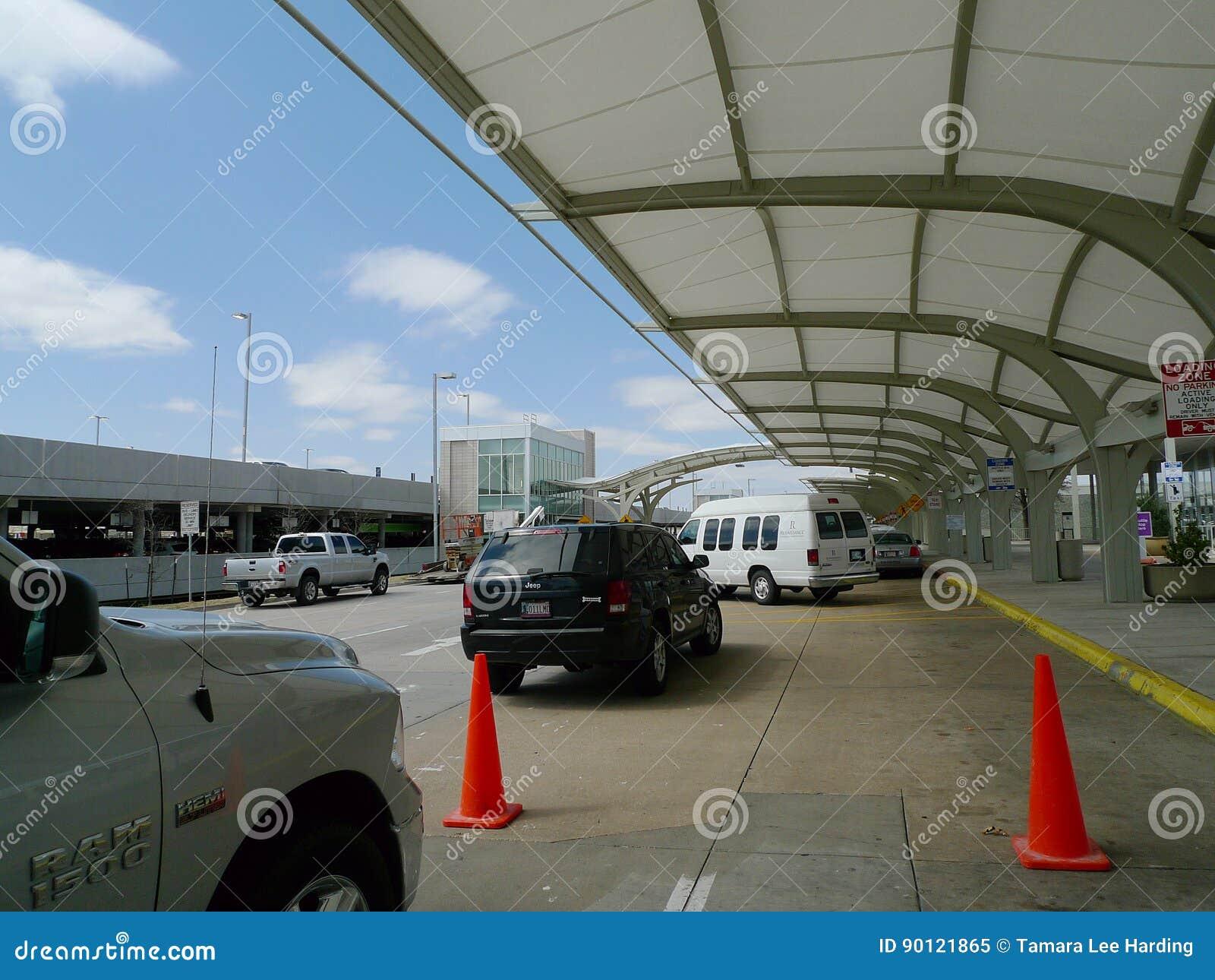 El d3ia exterior del aeropuerto internacional de Tulsa, vehículos adentro cae apagado el carril