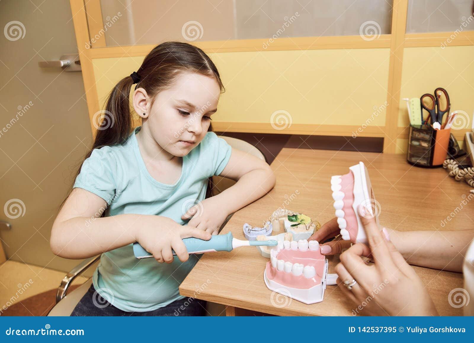 El dentista de la mujer enseña a la niña a cepillar sus dientes