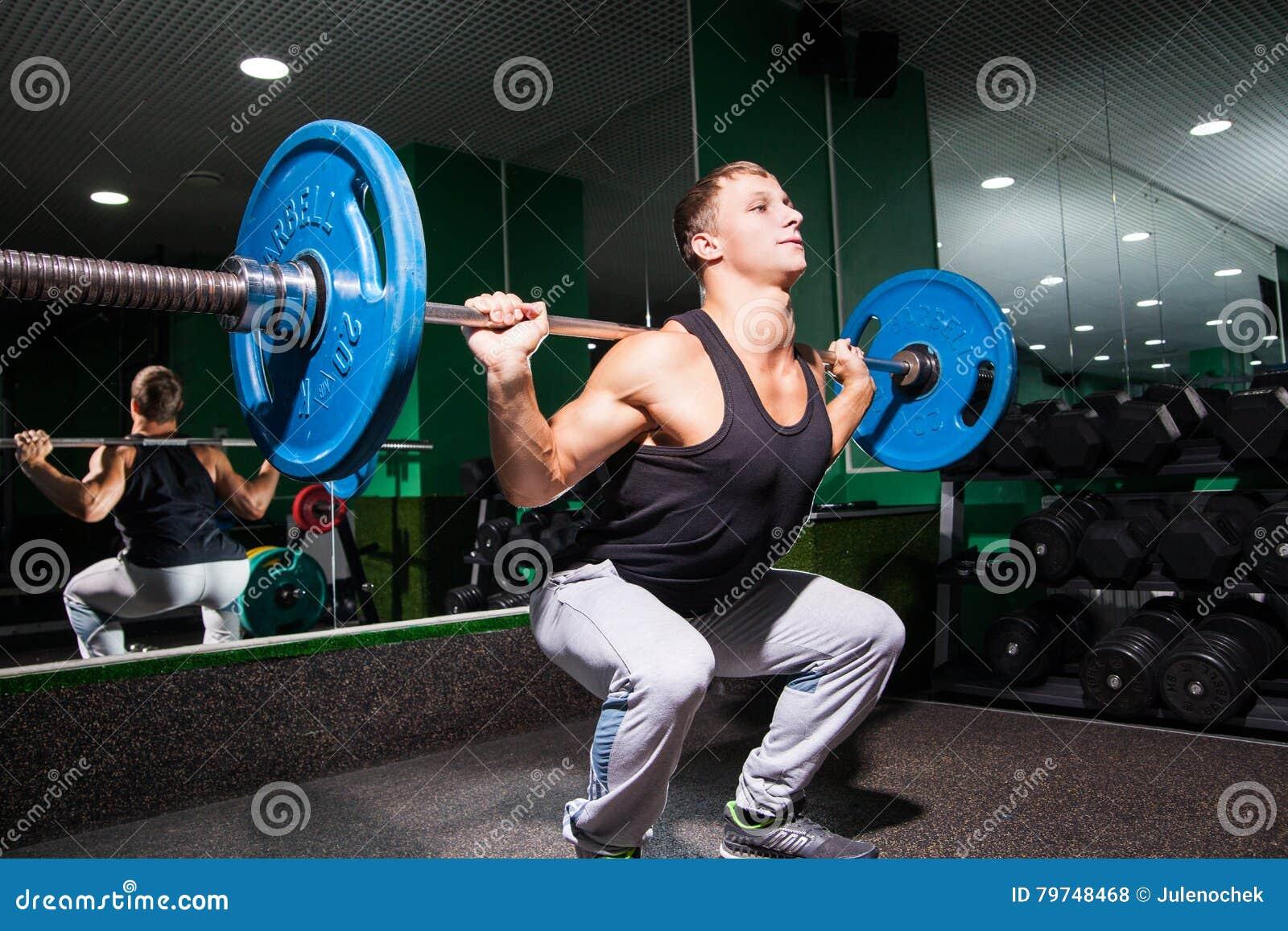 El deportista se pone en cuclillas en gimnasio