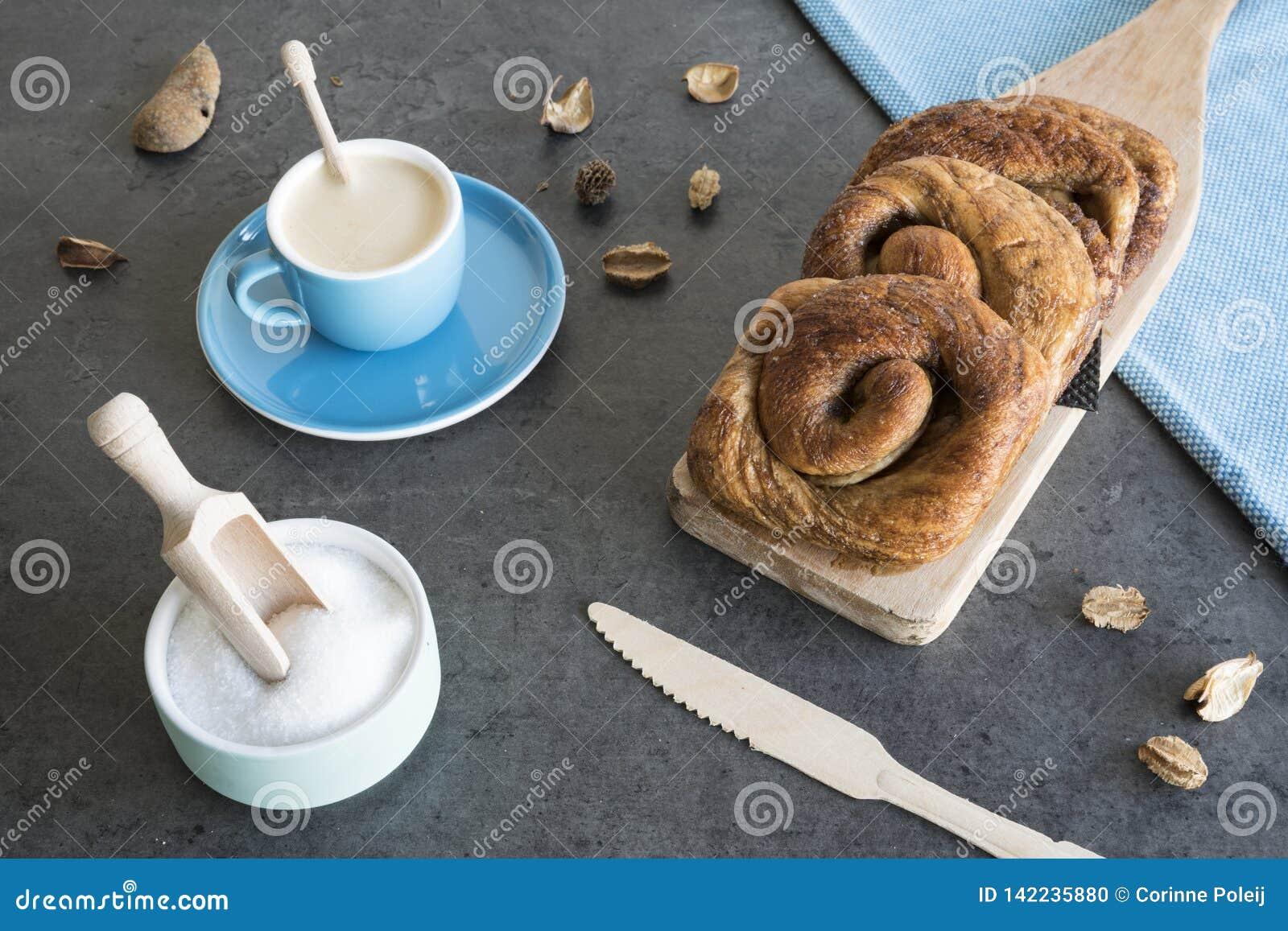 El desayuno con el rollo de pan holandés típico de canela llamó los 'bolos y la taza de café